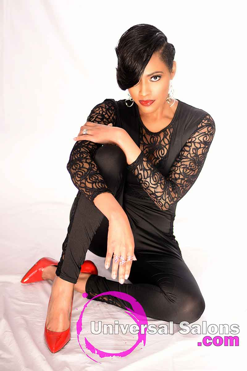 Model is wearing a short hair and bangs style and sitting with her leggs crossed.