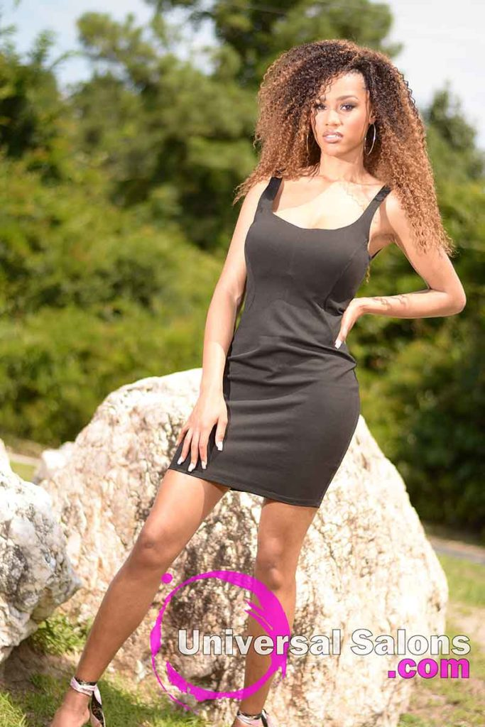 Model Standing With Long Curly Sew In Hairstyle With Hair Color