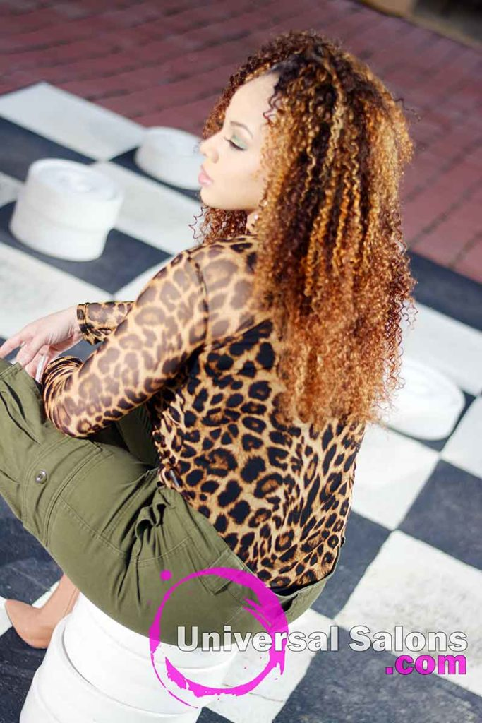 Model Sitting With Bohemian Curls Sew-In Hairstyle